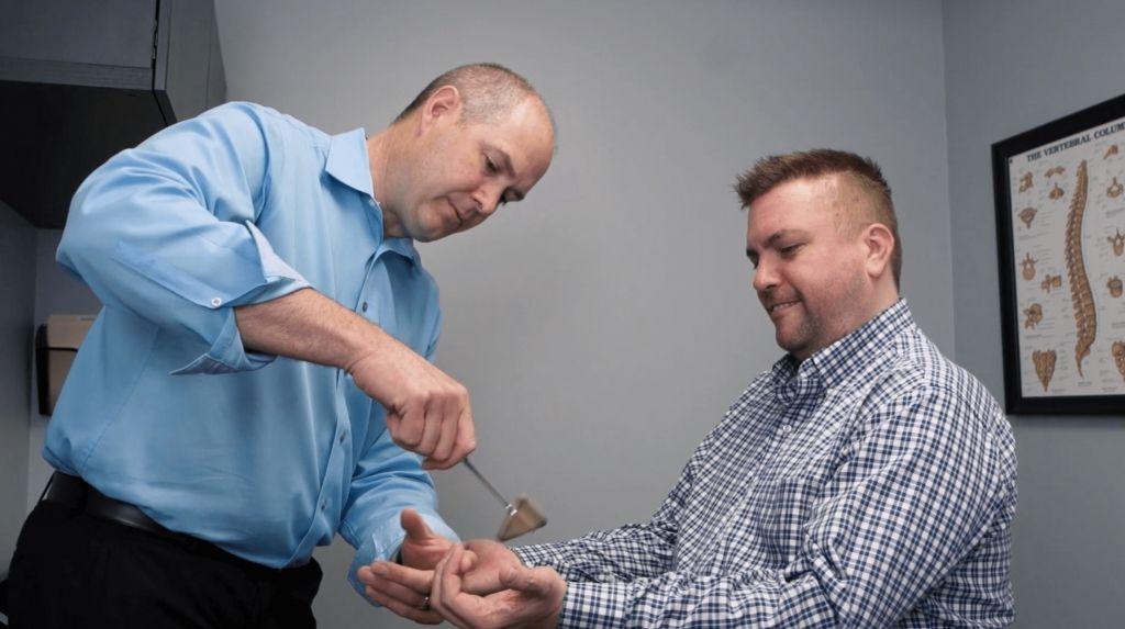 Dr. Pinckney checking reflexes on hand
