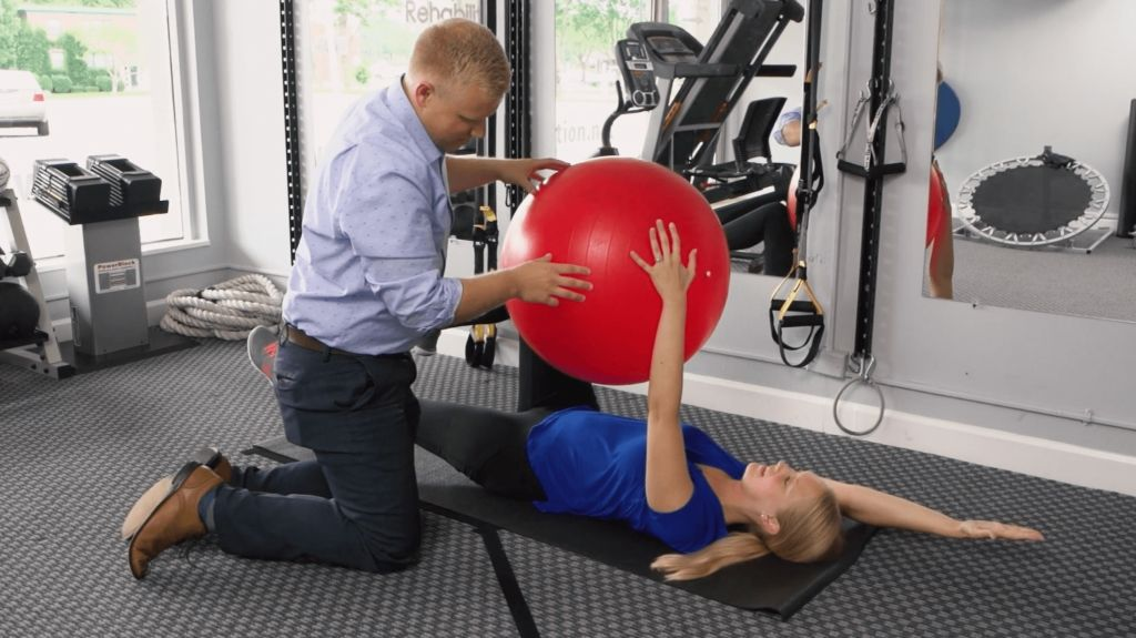 Dr. Douglas Ryan Evenhouse working one on one with a patient on core strength physical rehabilitation